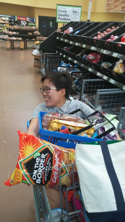A woman is laughing inside a grocery cart, with the groceries on top of her
