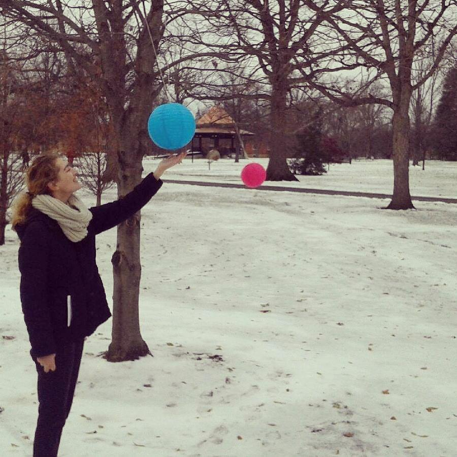 A girl touches a lantern hanging from a tree in the snow