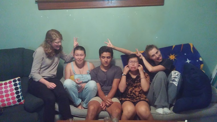 Five people on a couch make silly poses