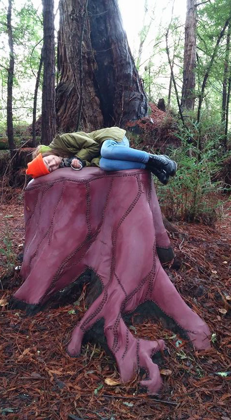 The author laying on a sculpture of a cut down trunk of a redwood tree amidst other real redwood trees