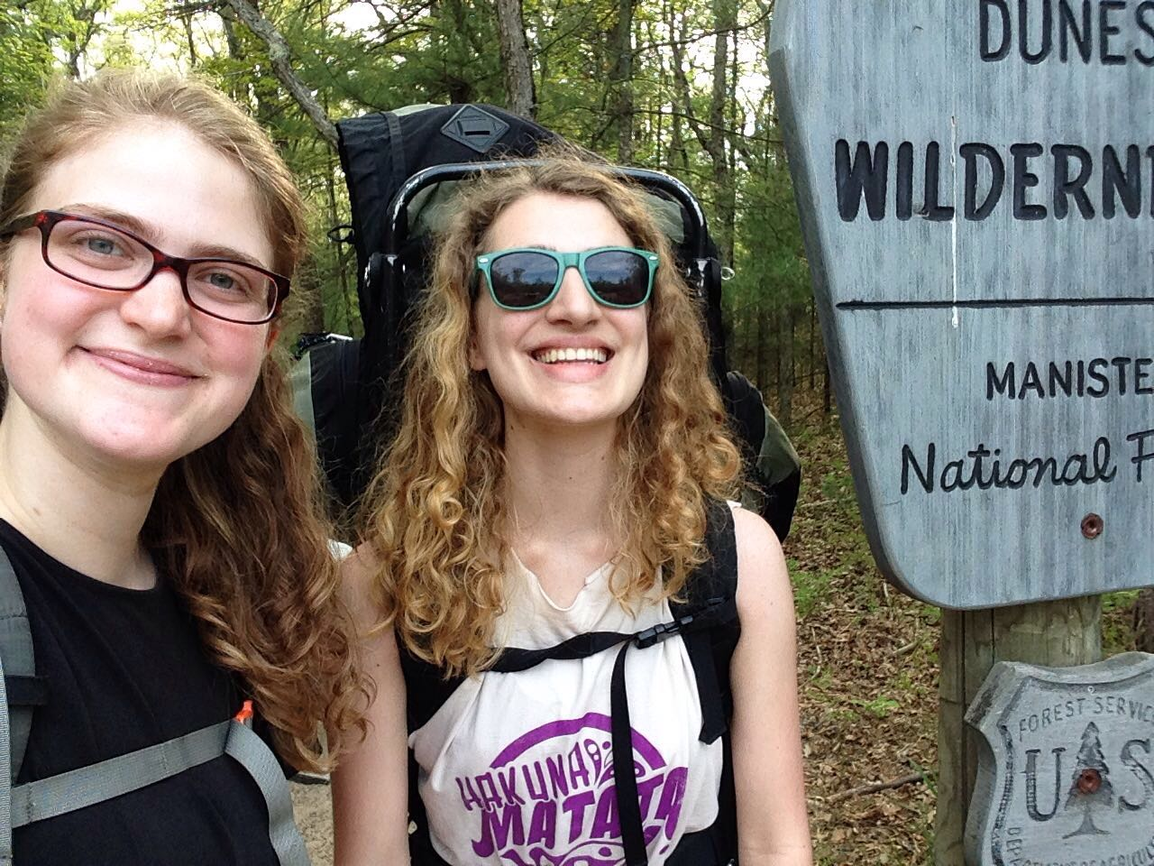 Author and friend taking a selfie with hiking packs on backs