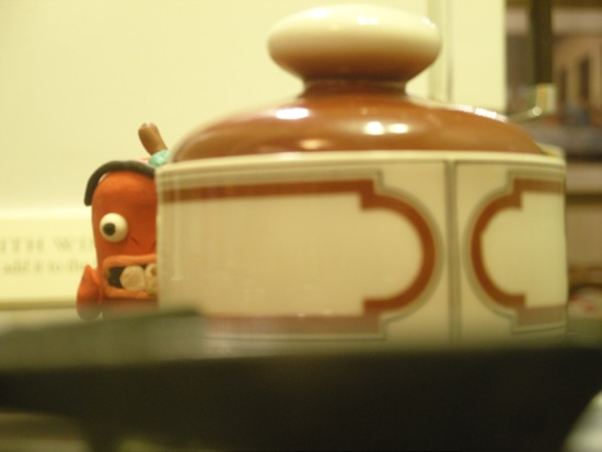 A clay figure is partially visible behind a pot.