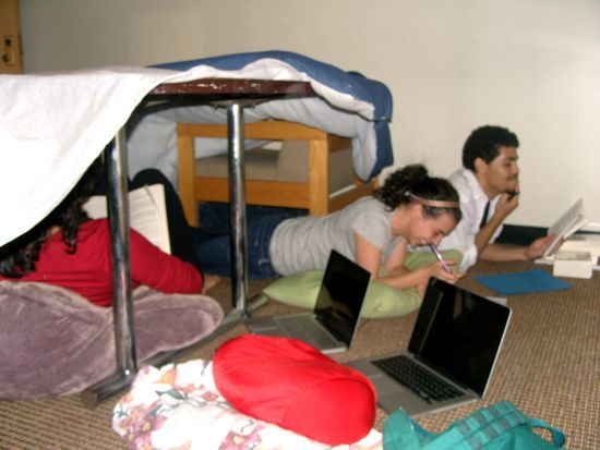 Inside the blanket fort, 3 people are studying.