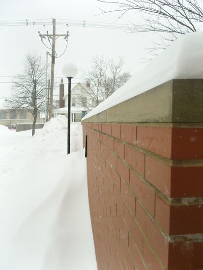 A mound of snow on a brick wall