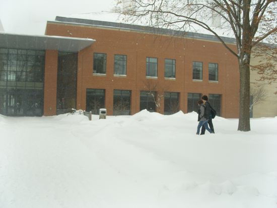 Two students walk on the sidewalk in front of the Science Center