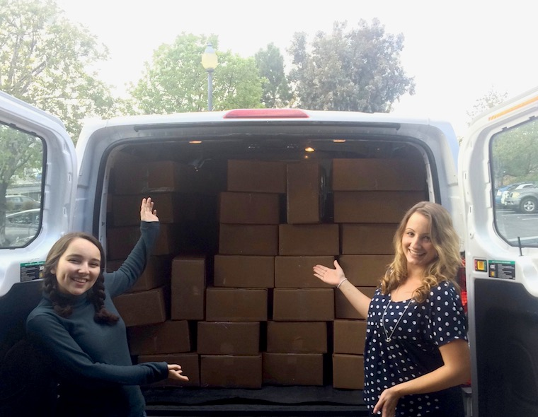 Kira and Jenny in front a truck full of boxes