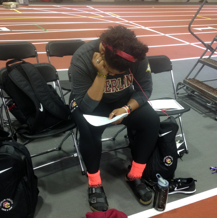 Seated on a folding chair by the track, a woman in an Oberlin sweatshirt looks down at a sheet of paper
