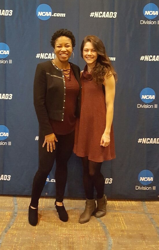 Two women pose. The backdrop has logos and hashtags for ncaa.com, NCAA Division III, and #NCAAD3