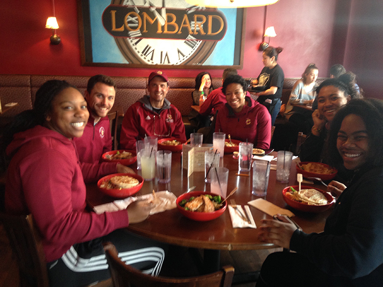 A group of people in Oberlin clothing are seated around a table at a restaurant