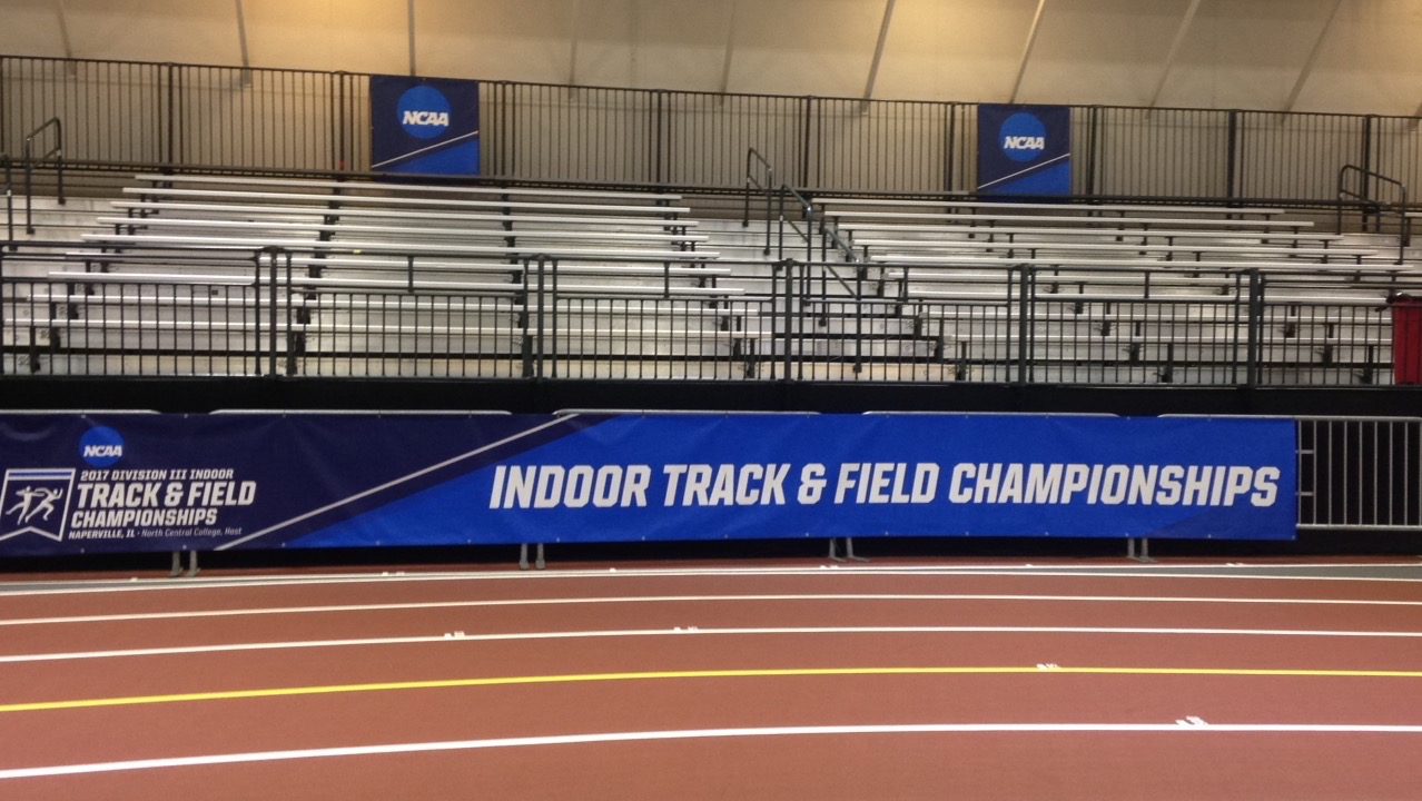 Empty stands behind a running track, with NCAA banners