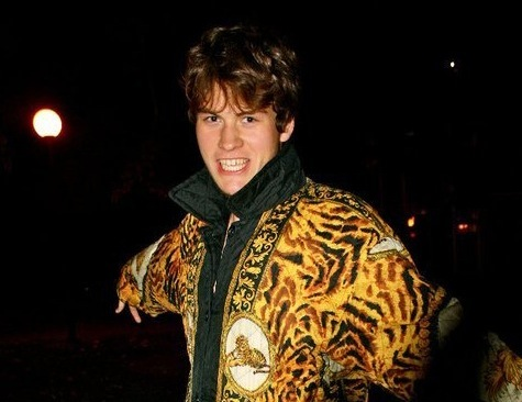 David Tisel wearing a leopard themed coat with their arms outstretched and looking at the camera
