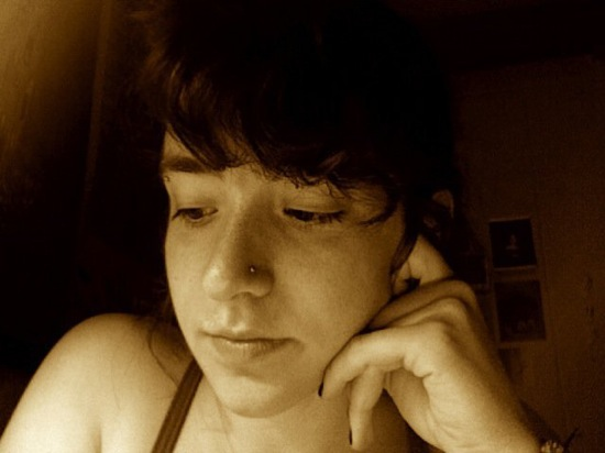 A sepia-toned picture of Hannah in a room with their hand resting on their cheek