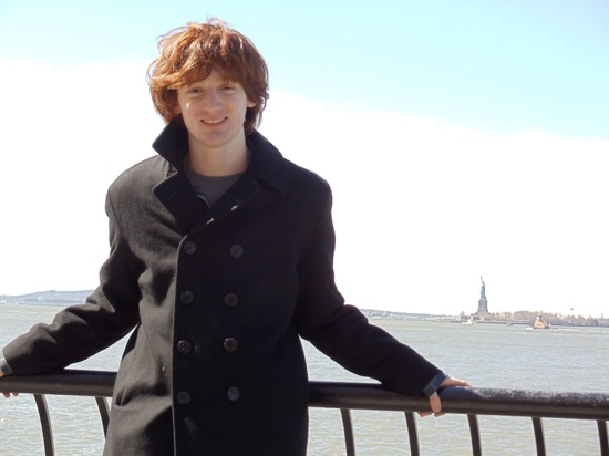 Logan poses at the railing overlooking the Statue of Liberty in the distance