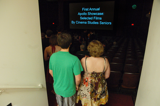 "Students walk into the theater. On screen: ""First Annual Apollo Showcse: Selected FIlm By Cinema Studies Seniors"""