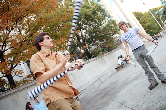Two student spins poi in front of a museum