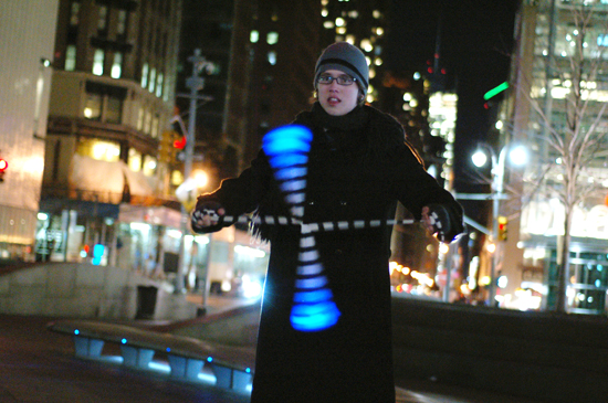 A student spins poi at night