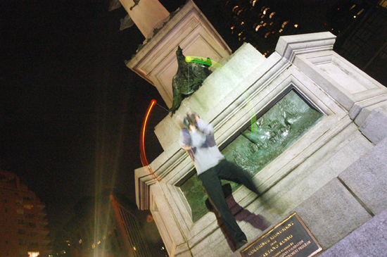 A student spins poi in front of a monument