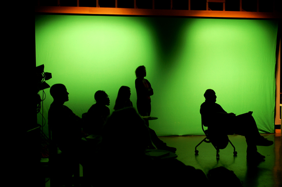Silhouette of people in front of a green screen.