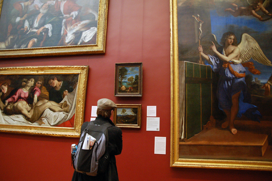 A person looking at various paintings in the Met's collection