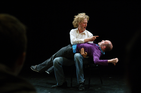 A performer lays across the lap of another in what seems to be an altercation