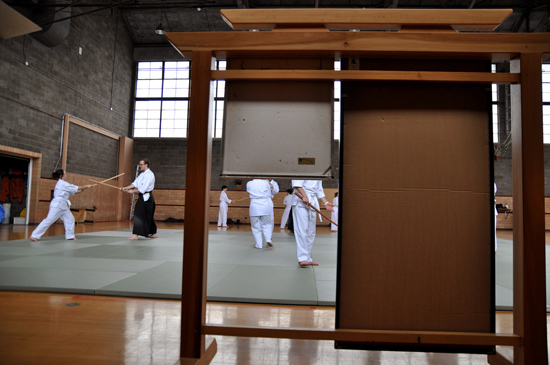 On mats in a gym, students wearing all white practice with wooden swords