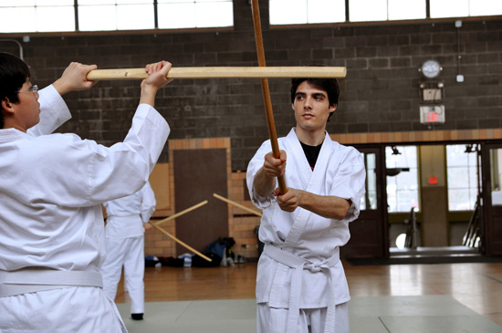 Two students practice with wood swords