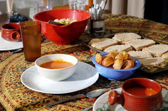 A table with a bowl of tomato soup and grilled cheese sandwiches