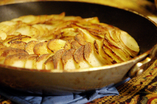 Close up shot of a galette of potatoes in a pan