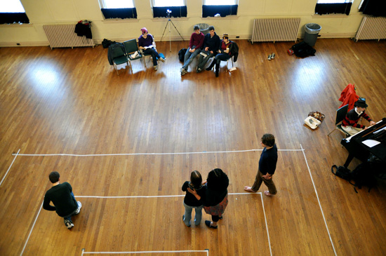 Performers rehearse in a large room with a wood floor, which has sections marked ou with tape.