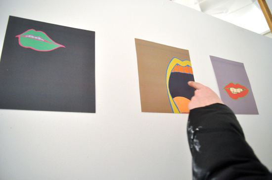 A finger pointing at prints hung on a wall