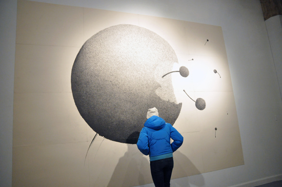 A viewer stands in front of an artwork