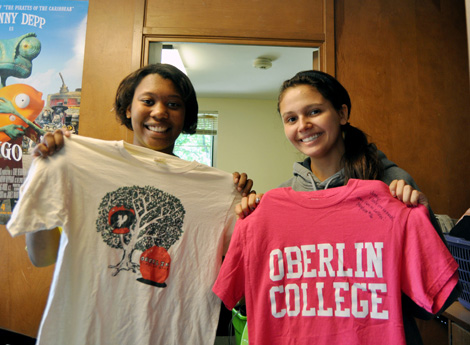 Two people hold up Oberlin t-shirts