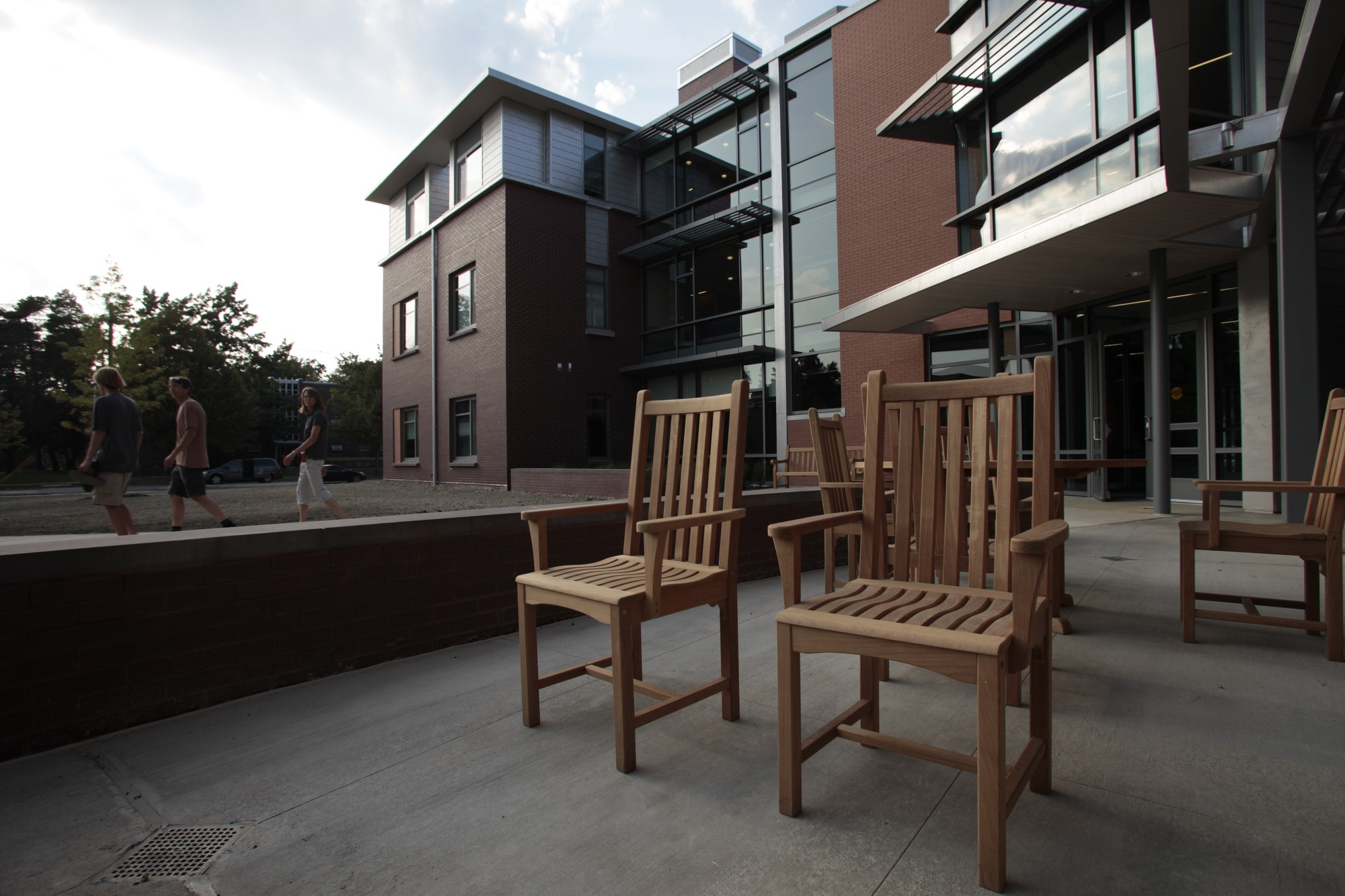 Wood chairs on a concrete patio outside a brick and glass building.