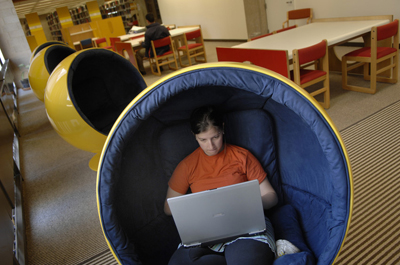 Student with laptop computer in a semi-spherical chair
