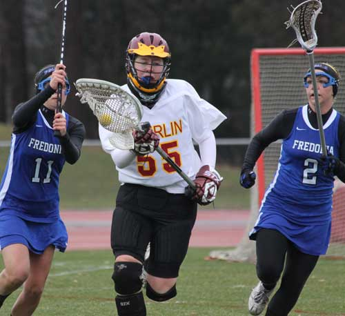 Oberlin women's lacrosse goalie running with the ball in a match
