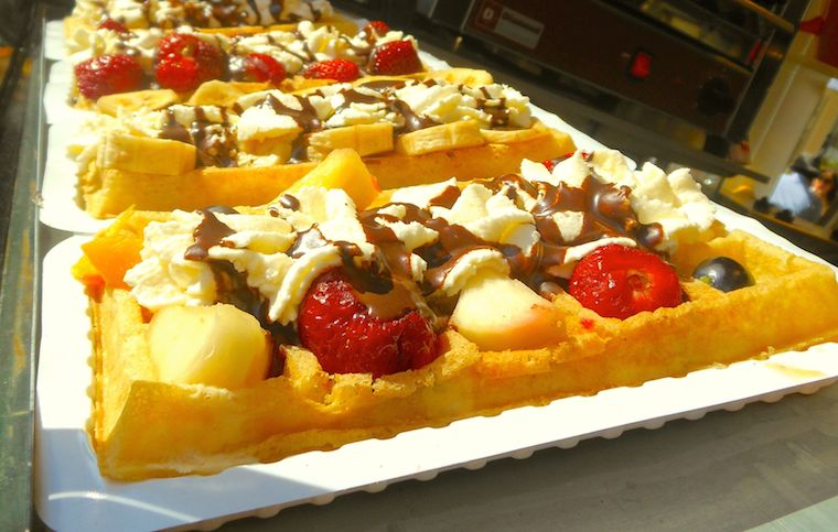 Waffle with fruit, whipped cream, and chocolate sauce