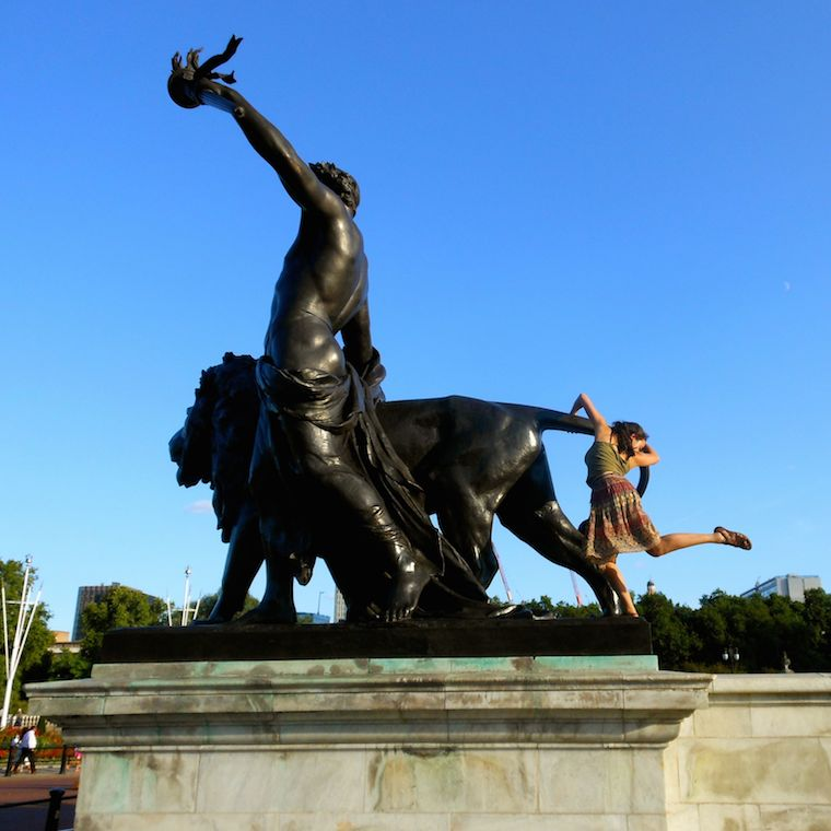 Student dancing next to a large statue