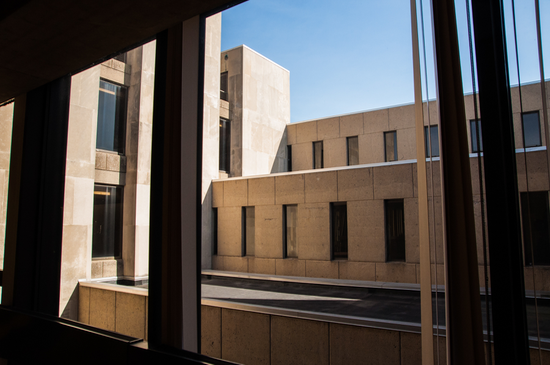 Looking out a window at Brutalist-style concrete walls and rectangular windows