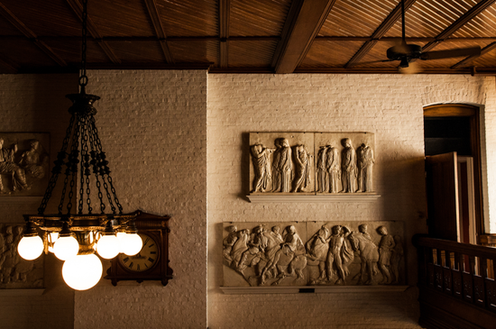 Relief sculptures on a wall by an old clock and a chandelier