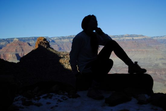 Someone sits on the edge of the grand canyon