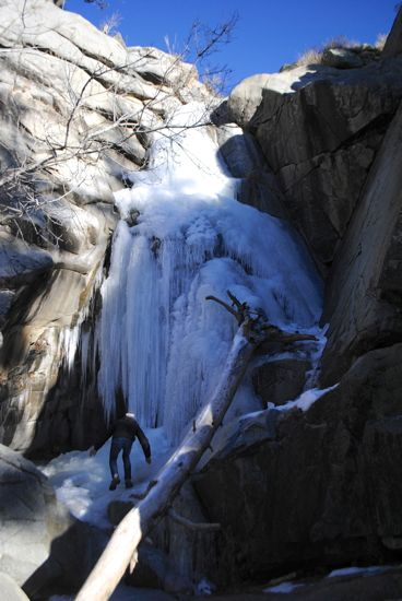 A frozen water fall with a hiker ascending
