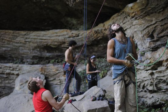 Bellay-ers assisting rock climbers at the base of a real-life rock wall