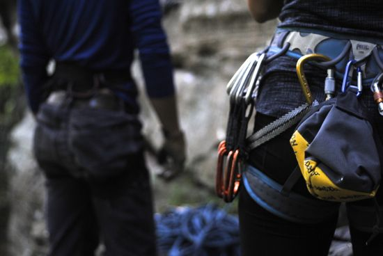 Carabiners hanging from the waist of a rock-climber