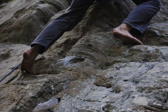 The feet of a rock climber climbing on a real-life rock wall
