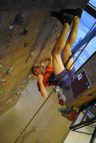 A rock climber hanging upside down at the phillips gym rock climbing wall