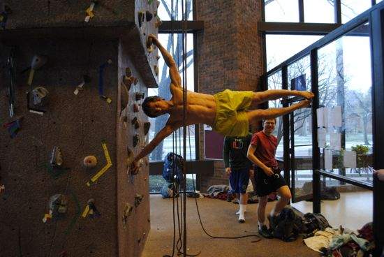 The rock climbing wall in Phillips gym. A climber is free climbing without a harness and is positioned horizontal to the ground