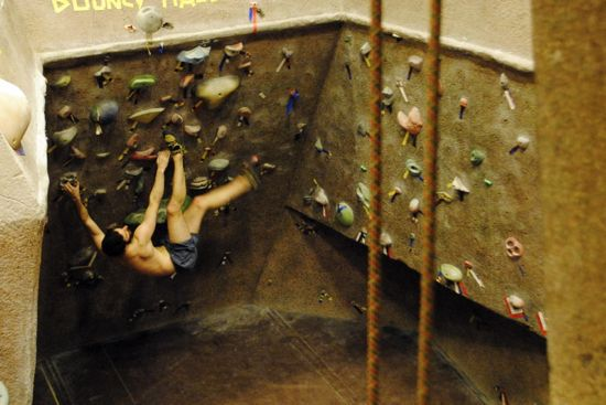 The rock climbing wall in Phillips gym. A climber is free climbing without a harness