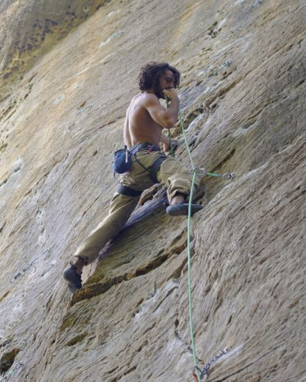 A climber rock climbing on a real-life rock wall