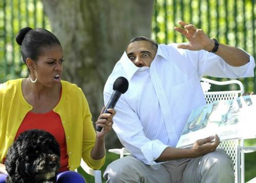 President Barack Obama reading the book Where the Wild Things Are to a group of children. He is making a silly face and his collared shirt is pulled up to his ears. First Lady Michelle Obama sits next to him, making a silly face and holding a microphone to The Presidents mouth