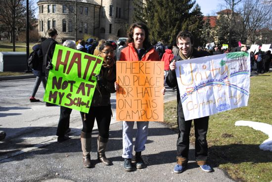 "Three students hold protest sign: ""There is no place for hate on this campus"""
